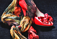 a red shoe with a bow in front, on top and in front of it, a silk scarf in yellow,green,orange,red and yellow. Placed on a black backdrop