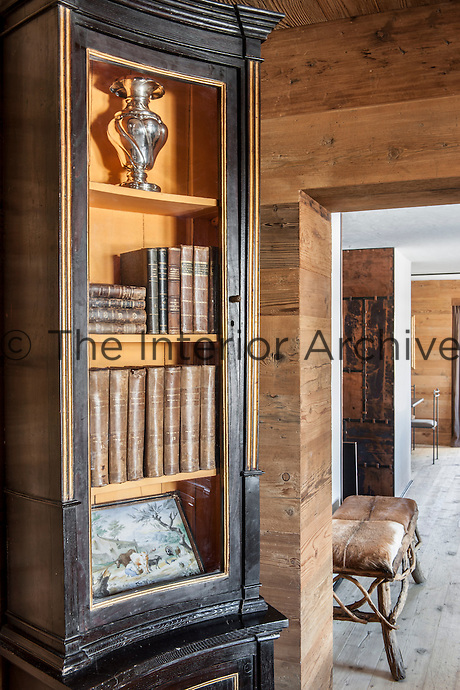 A collection of old volumes, a vase and a small painting are displayed in an antique French pharmacy cabinet beside the sitting room