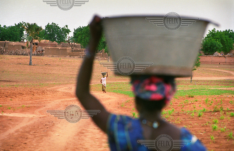 Women walk home with buckets of water on their heads. They have to walk more than a kilometre between the well and home several times a day. Traditionally, water transportation is a woman's job, one of such importance that many girls are kept from attending school.