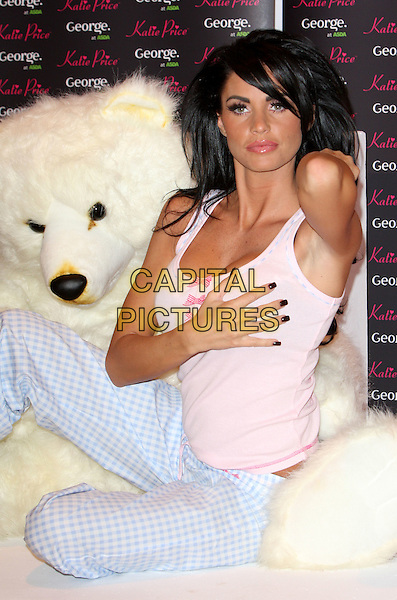 JORDAN - KATIE PRICE.Launches her new range of Nightwear at Worx Studio, Fulham, London, England..December 17th, 2008.half length pink tank top hand on chest breast touching grabbing nail varnish polish sitting blue check checked trousers .CAP/ROS.©Steve Ross/Capital Pictures.