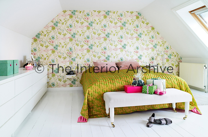 A fresh green, blue and pink floral wallpaper has been used to decorate the master bedroom, matched with a green and pink silk quilt