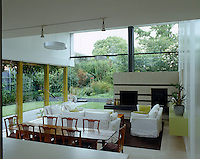 Touches of lime green used in the decoration of the open-plan living area visually link the interior with the garden