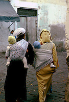 Two women carrying babies  on their backs.Cassablanca,Morocco, 1975