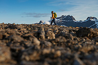 Female hiker hiking over rocky slopes near summit of Hestræva, Flakstadøy, Lofoten Islands, Norway