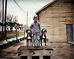 "To pose this pair of fine hounds atop their doghouse, the photographer has enlisted the services of a boy in a crooked-buttoned cardigan sweater. Some of the most captivating photographs are those where children are center-stage. In spite of their often tattered clothing, children are never depicted as downtrodden or ""less than"". Rather, they have a special nobility."