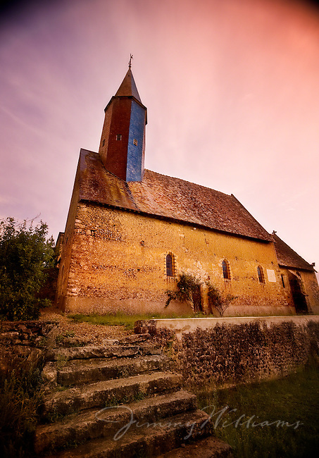 An old stone church with beautiful steeple sits on top of an ancient stone foundation in the farmlands of France