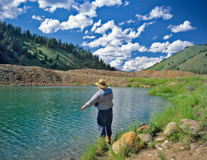 Fly fisherman casting to trout on pond in Sawtooth National Recreation Area, Idaho.