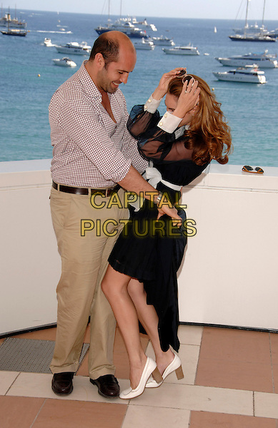 "BILLY ZANE & KELLY BROOK.Photocall for ""Fishtales"" starring Kelly as a mermaid at the  60th International Cannes Film Festival, Cannes, France.  May 17th , 2007.full length sunglasses shades black sheer sleeves dress white stripe sash collar belt beige trousers red plaid shirt couple profile funny gesture.CAP/PL.©Phil Loftus/Capital Pictures."