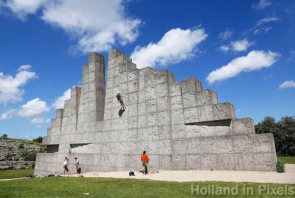 Nederland, Amsterdam. In recreatiegebied Spaarnwoude (tussen IJmuiden, Haarlem en Amsterdam) bevindt zich een kunstobject dat ontworpen is door de Leidse beeldhouwer Frans de Wit in nauwe samenwerking met klimmer Ad van der Horst. Het object is een klimmuur en heeft als doel kunst en recreatie te integreren. De klimmuur bestaat uit 178 betonblokken van 1,2m bij 1,2m. Deze blokken zijn afgietsels van rotsen in de buurt van Namen, bij Marche-les-Dames in België.