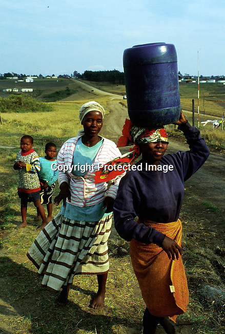 Margarette Shenge, 36, with her daughter Zethu,16, on October 25, 1999  walking home after fetching water close to their one-room house in Nqbeni, Southern Natal South Africa. Margarette and two of her four children are infected by the Aids virus. The father died of Aids in 1997..(Photo: Per-Anders Pettersson/ Liaison Agency)