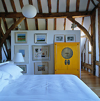 A collection of artwork on a floating wall and a bright yellow Chinese cupboard in the bedroom