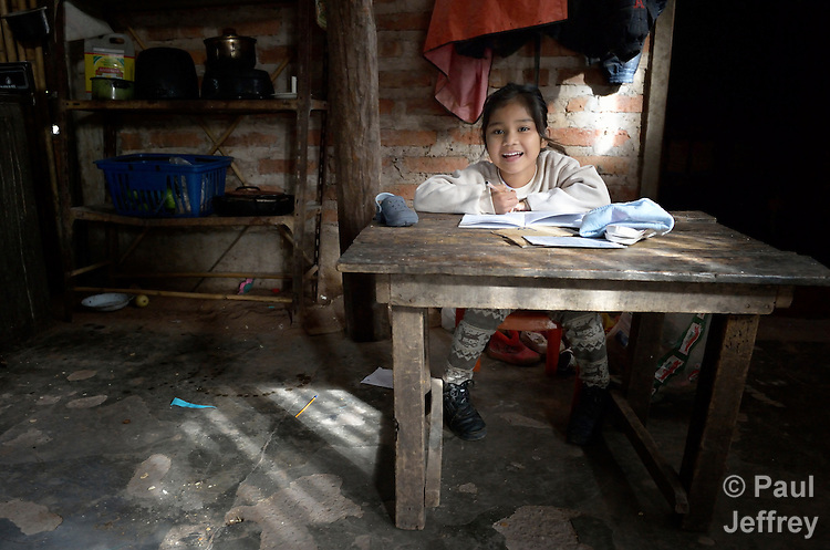 Valentina Romero, 5, is a Guarani indigenous girl in Bananal, a small village in the Chaco region of Argentina where residents have struggled to defend their land and their rights against giant agro-export plantations and cattle raisers. The girl has enrolled in pre-school and is doing her homework in the kitchen of her family's house.
