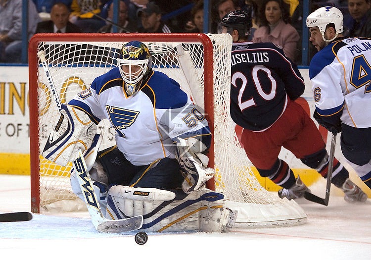 March 28 2009     Blues goalkeeper Chris Mason (50, left) watches the puck scott across the front of the goal as teammate Roman Polak (46, center) and Blue Jackets player Kristian Huselius (20, right) skate around the goal in second period action.   The St. Louis Blues hosted the  Columbus Blue Jackets March 28, 2009 at the Scottrade Center in downtown St. Louis, Missouri...            *******EDITORIAL USE ONLY*******