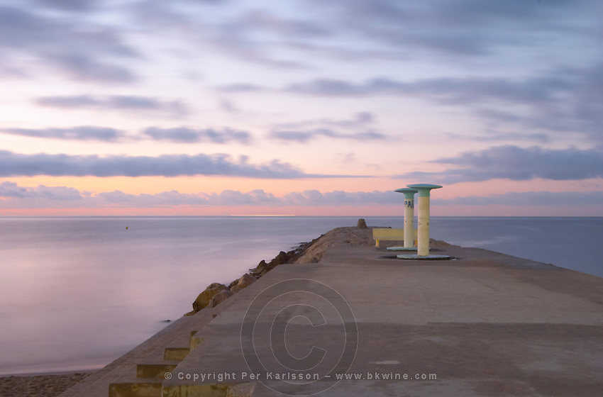 A pier with two showers in evening light. Sitges, Catalonia, Spain