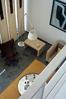 A view down to a neutrally furnished living room from the mezzanine floor above