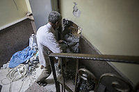 A Syrian volunteer drills a wall in the lower level of the Dar Al-Shifa hospital to open an emergency exit towards the next-door building in case of an air raid. September 27, 2012.