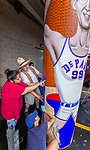 "Naomi Maturino, Brother Mark Elder, C.M., and Emily Spurgeon '16 (below) gather with other artists, Saturday, July 28, 2018, as they install the first of three new murals under the Fullerton ""L"" Station in Lincoln Park. The caricature of DePaul basketball star George Mikan, a 1959 Naismith Memorial Basketball Hall of Fame inductee, was installed on a pillar directly under the CTA's Brown and Purple Line. Later in the day, the group installed a mural featuring a montage of historical images highlighting the 50th anniversary of DePaul's Black Student Union, then one around a column celebrating the opening of the university's Loop Campus.<br /> <br /> Elder's artistic retrospective, titled ""The Story of 'The Little School Under the 'L'', will eventually feature 25 murals permanently installed on the massive concrete pillars that support the ""L"" station nearest the university's Lincoln Park Campus. (DePaul University/Jamie Moncrief)"