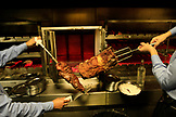 BRAZIL, Rio de Janiero, servers hold up the freshly cooked meat at Fogo de Chao Restaurant, Botafogo