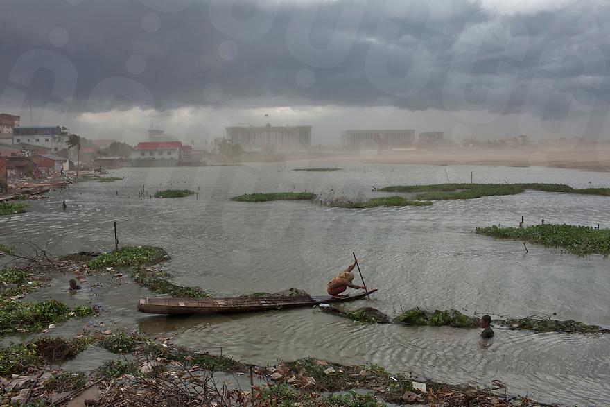 July 07, 2011 - Phnom Penh, Cambodia. A woman rows a boat against the wind as a storm comes in over Boeung Kak. © Nicolas Axelrod / Ruom