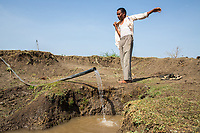 Lake Kava, the largest body of water close to the city of Latur has dried up completely. A farmer looks over a water pipe feeding water onto his land.