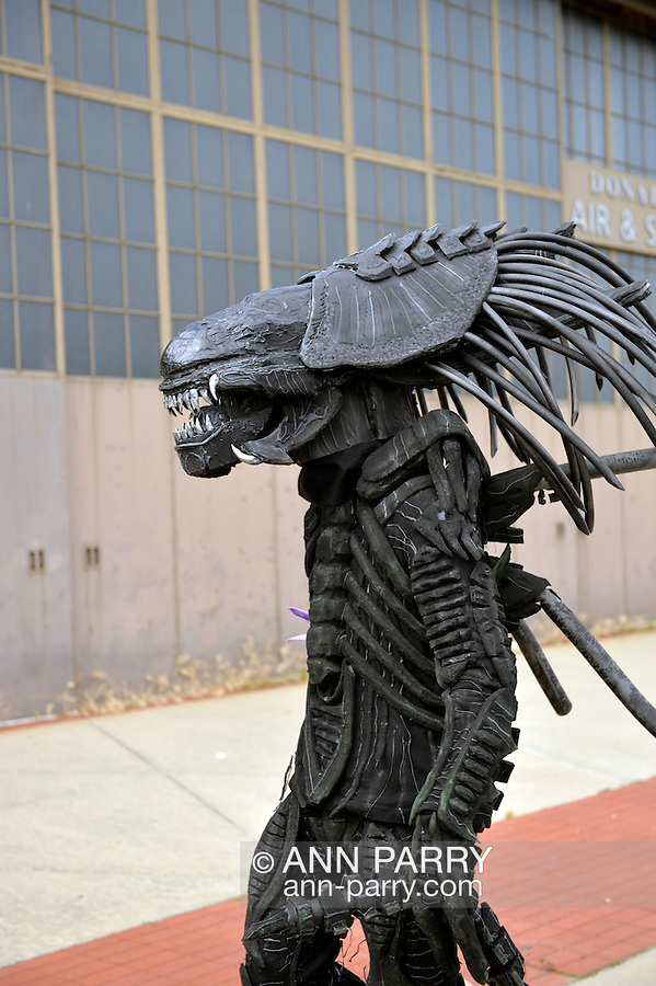 Garden City, New York, U.S. - June 14, 2014 - A man in an Alien costume, based on Alien VS Predator movie, walks in front of an historic Mitchel Field hangar at Eternal Con, the annual Pop Culture Expo, with costumes, Comic Books, Collectibles, Gaming, Sci-Fi, Cosplay, Horror, and held at the Cradle of Aviation Museum on Long Island.