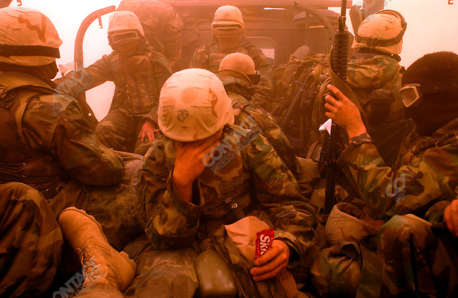 As a sandstorm blew troops from Ist Marine Division rested,some sleeping, some eating, some just adjusting goggles, as their truck halted on the road north to Baghdad, not from from the southern city of Nasiriya. March 25, 2003