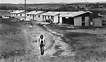 A Lakota teenager seen walking near a public housing project on the Pine Ridge Reservation in South Dakota, in 1983. Photo by Jim Peppler. Copyright/Jim Peppler/.