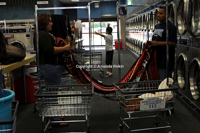 Customers folding laundered item in the World's Largest Laundromat in Berwyn, Illinois on July 7, 2008.