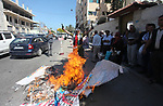 Palestinians burn an Israeli, British and U.S. flags during a protest to show solidarity with Palestinian prisoners held in Israeli jails, in front of Red cross office in Gaza city on June 25, 2018. Photo by Mahmoud Ajour