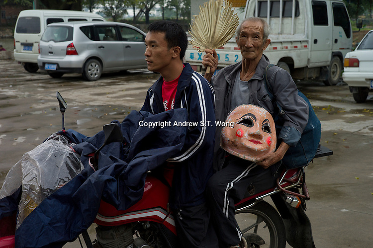 An elderly master leaves on motorbike after performing the traditional Big Head Buddha dance in front of the ancient ancestral temple at Yanqiao village in Nanhai district of Foshan city, Guangdong province, November 8, 2011.