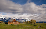 Bright, puffy cumulus clouds fill the sky over the Tetons and this barn in Mormon Row.