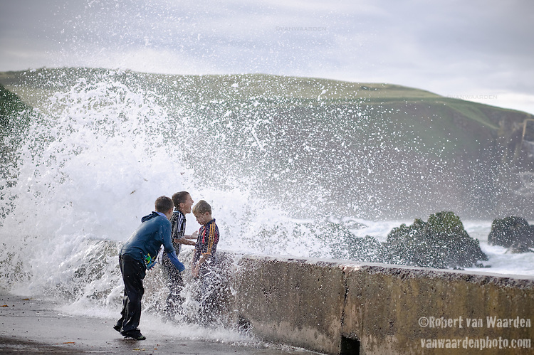 Three boys are splashed by a huge wave in St. Abbs, Scotland. In typical summer fun, the boys enjoyed getting soaked by the waves that came crashing over the break water.