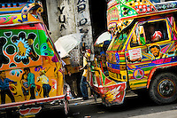 Tap-tap buses wait to get full and depart for their regular route in the downtown of Port-au-Prince, Haiti, 25 July 2008. Tap-tap vehicles serve as public transportation in Haiti. They are private, operate over fixed routes, departing only when full. Tap-taps are decorated with bright and shiny colors and with a lot of fancy designed elements. There are scenes from the Bible, Christian slogans, TV stars or famous football players often painted on a tap-tap body. Tap-tap name comes from sound of taps on the metal bus body signifying a passenger's request to be dropped off.