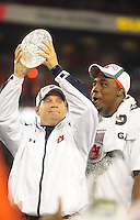 Jan 10, 2011; Glendale, AZ, USA; Auburn Tigers head coach Gene Chizik hoists the Coaches Trophy as defensive tackle Nick Fairley (90) celebrates following the game against the Oregon Ducks in the 2011 BCS National Championship game at University of Phoenix Stadium. Auburn defeated Oregon 22-19. Mandatory Credit: Mark J. Rebilas-