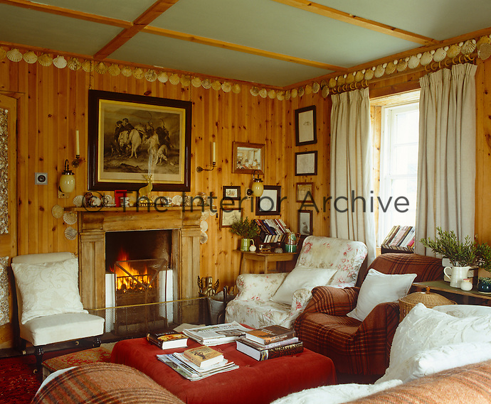 The living room is lined in golden pine edged with scallop shells and glows in the warmth of an open fire