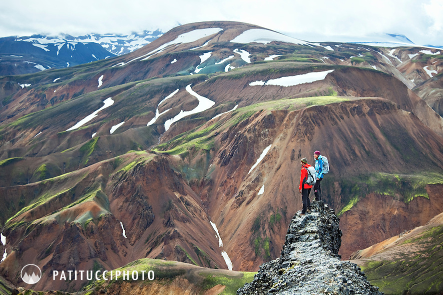 Two hikers on the summit of Blahnukur Peak, high above Landmannalaugar, Iceland. The unique landscape of Iceland is spread out behind and beneath them.