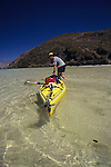 A young man pulls his sea kayak through shallow water in Bahia Conception, Sea of Cortez, Mexico.