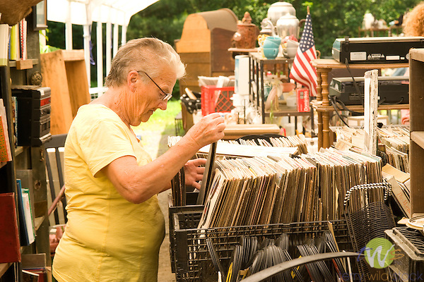 Woman searching old vinyl records at flea market.