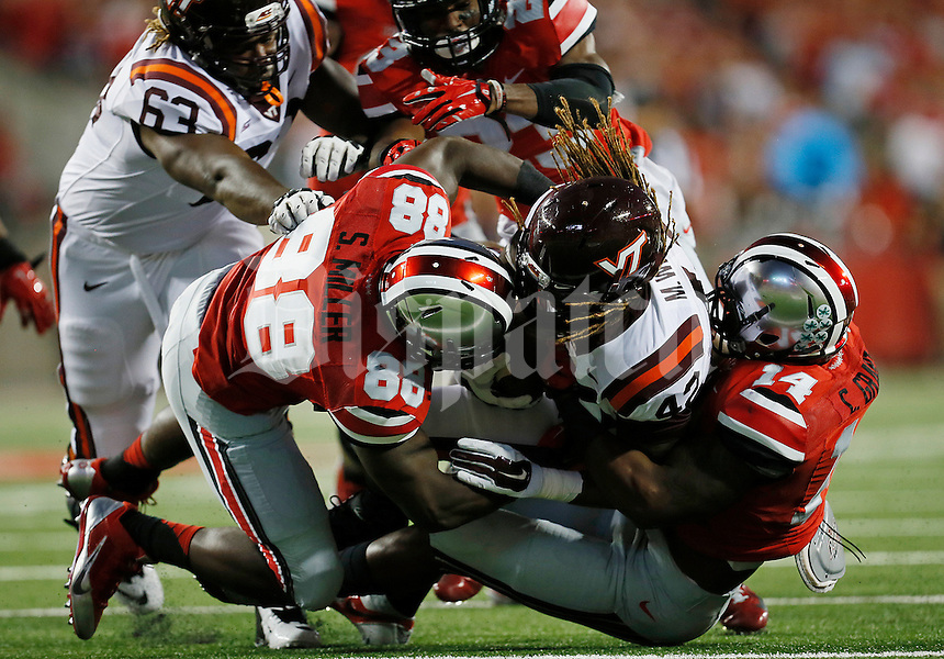 Ohio State Buckeyes defensive lineman Steve Miller (88) and Ohio State Buckeyes linebacker Curtis Grant (14) take down Virginia Tech Hokies running back Marshawn Williams (42) in the first quarter of the college football game between the Ohio State Buckeyes and the Virginia Tech Hokies at Ohio Stadium in Columbus, Saturday afternoon, September 6, 2014. The Virginia Tech Hokies defeated the Ohio State Buckeyes 35 - 21. (The Columbus Dispatch / Eamon Queeney)