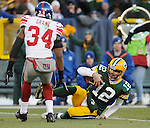 Green Bay Packers quarterback Aaron Rodgers slides for a first down near New York Giants' Deon Grant during the first quarter of the game at Lambeau Field in Green Bay, Wis., on Dec. 26, 2010.