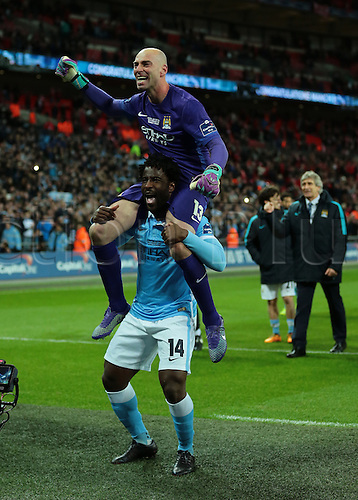 28.02.2016. Wembley Stadium, London, England. Capital One Cup Final. Manchester City versus Liverpool. Manchester City Forward Wilfried Bony carries hero of the hour Manchester City Goalkeeper Wilfredo Caballero on his shoulders, as Manchester City Manager Manuel Pellegrini celebrates in the background