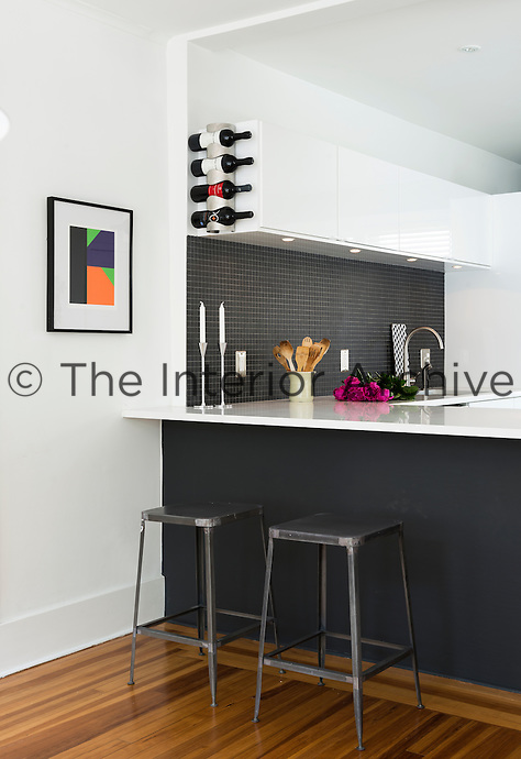 A modern, grey and white kitchen with a peninsula unit incorporating a breakfast bar where two metal stools are placed below.