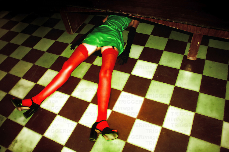 A young woman wearing bright green stockings lying on a tiled floor