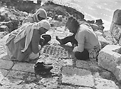 game played with stones on a board in the ground, Arab fishermen playing a game,