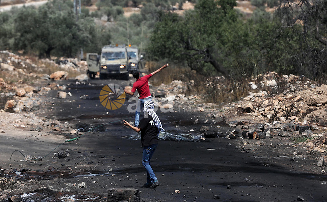 Palestinian protesters hurl stones towards Israeli security forces during clashes  following a weekly demonstration against the expropriation of Palestinian land by Israel in the village of Kfar Qaddum, near Nablus, in the occupied West Bank on June 30, 2017. Photo by Ayman Ameen