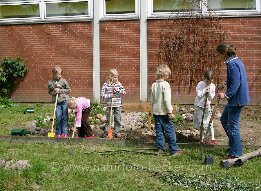 Schulgarten, Anlage eines Schmetterlingsgarten, Garten der Grundschule Nusse wird als Projektarbeit von einer 1. Klasse gestaltet, Kinder und Lehrerin arbeiten in den Beeten, Gartenarbeit
