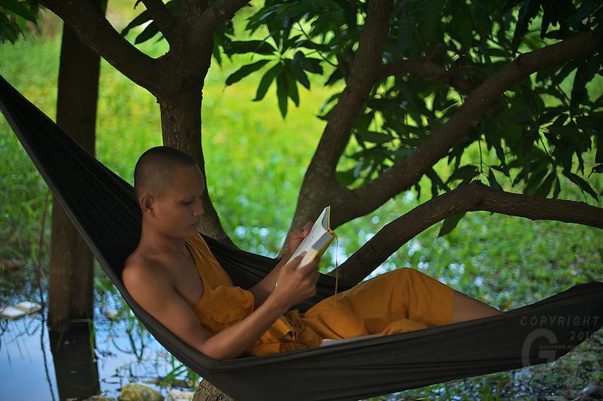Monk reading and studying in a hanging mat Battambang, Cambodia