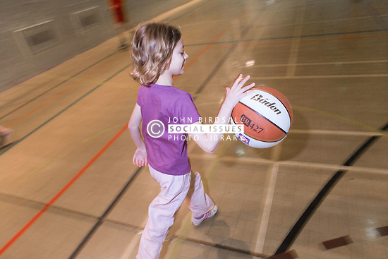 Young girl playing a game of basket ball in the sports hall of her local leisure centre,