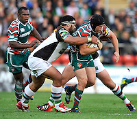 Leicester, England. James Johnston of Harlequins tackles Julian Salvi of Leicester Tigers tackled during the Aviva Premiership match between Leicester Tigers and Harlequins at Welford Road on September 22, 2012 in Leicester, England.