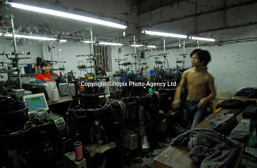 """Xuan Lou Fei, 28, a local man who has set up his own small factory in an old village farm-house in Datong """"sock city"""" in Zhejiang Province, China.  The town in Zhejiang Province makes more than 5.3 billion pairs of socks annually - that 2.5 pairs for every human alive.  Most people in the town make a living directly conected to the sock weaving industry."""
